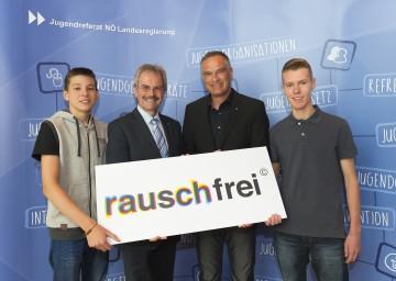 """Landesrat Mag. Karl Wilfing und Projektleiter Mario Leiter (von links), flankiert von zwei Schülern, bei der Präsentation der Bilanz über zehn Jahre Präventionsaktion """"Rauschfrei""""."""