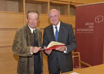"""Landeshauptmann Dr. Erwin Pröll und Autor Julian Schutting bei der Übergabe des Vorlasses an das \""""Archiv der Zeitgenossen\"""" in Krems."""