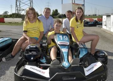 Landesrat Dr. Stephan Pernkopf und Dr. Herbert Greisberger von der eNu mit drei Jugendlichen beim Elektro-Kart Rennen.