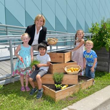 Landesrätin Mag. Barbara Schwarz freut sich gemeinsam mit den Kindergartenkindern über die reiche Ernte der Erdäpfelpyramide.
