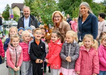 Bürgermeister Johann Rädler, Landeshauptfrau Johanna Mikl-Leitner, Leiterin Sabina Doria (v.i.n.r.) und die Kinder von Bad Erlach freuen sich über den neuen Landeskindergarten.