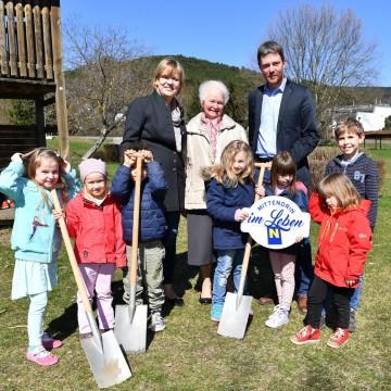 Landesrätin Mag. Barbara Schwarz und Bürgermeister Roland Braimeier freuen sich mit den Kindern, Seniorinnen und Senioren auf den entstehenden Generationenpark in Markt Piesting.