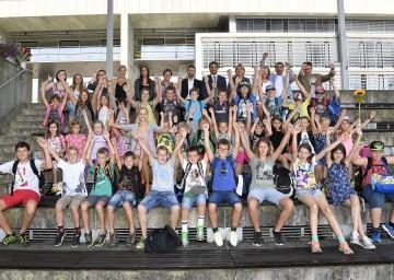 Landesrätin Mag. Barbara Schwarz freut sich gemeinsam mit zahlreichen Kindern und Sponsoren über eine spannende Ferienbetreuung.