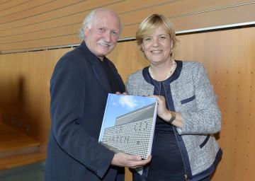 """Landesrätin Mag. Barbara Schwarz und Lois Lammerhuber mit dem Buch """"Kinder (!) Gärten""""."""